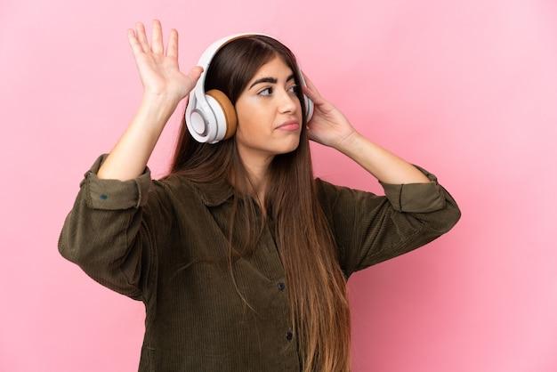 Mujer joven aislada en la pared rosa escuchando música y bailando