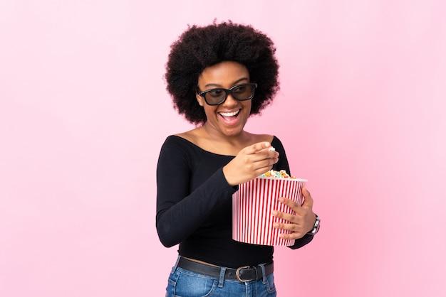 Mujer joven aislada en rosa con gafas 3d y sosteniendo un gran cubo de palomitas mientras apunta hacia adelante
