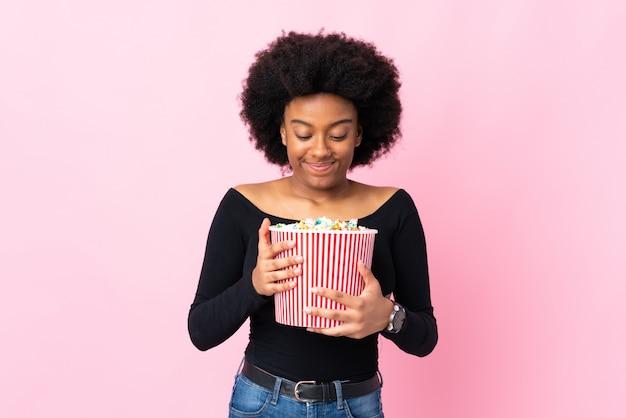 Mujer joven aislada en rosa sosteniendo un gran cubo de palomitas de maíz