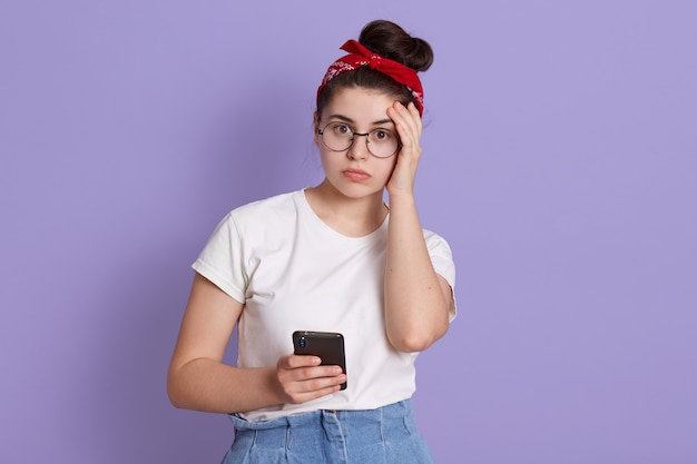 Mujer joven aislada sobre una pared púrpura con expresión facial preocupada, sosteniendo un teléfono inteligente roto, vistiendo una camiseta blanca casual y una banda para el pelo roja
