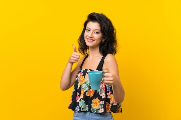 Mujer joven aislada en la taza de café caliente de la explotación agrícola amarilla
