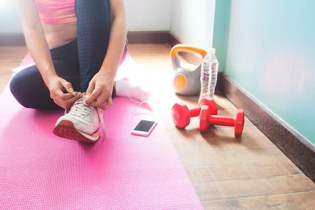 Mujer joven del ajuste sano en el activewear que prepara el ejercicio en casa, concepto sano