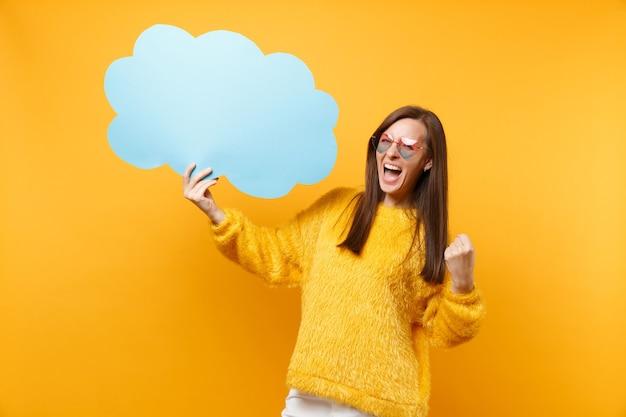 Mujer joven alegre en anteojos de corazón mantenga azul en blanco vacío diga bocadillo de diálogo de nube haciendo gesto de ganador gritando aislado sobre fondo amarillo. personas sinceras emociones, estilo de vida. área de publicidad.
