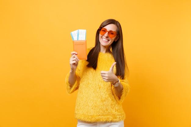 Mujer joven alegre en anteojos de corazón naranja mostrando el pulgar hacia arriba, sosteniendo pasaporte y boletos de tarjeta de embarque aislados sobre fondo amarillo brillante. personas sinceras emociones, estilo de vida. área de publicidad.