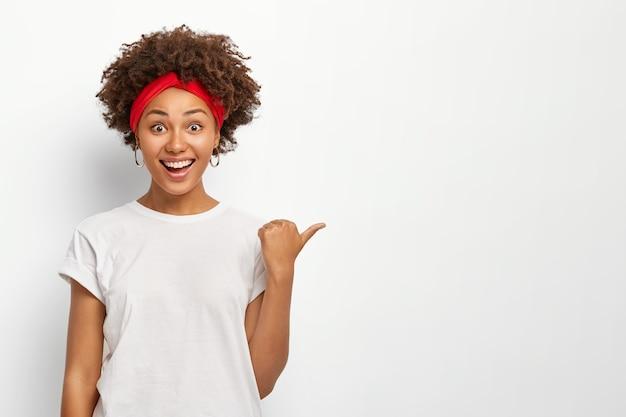 Mujer joven alegre apunta a la derecha con el pulgar, vestida con ropa casual