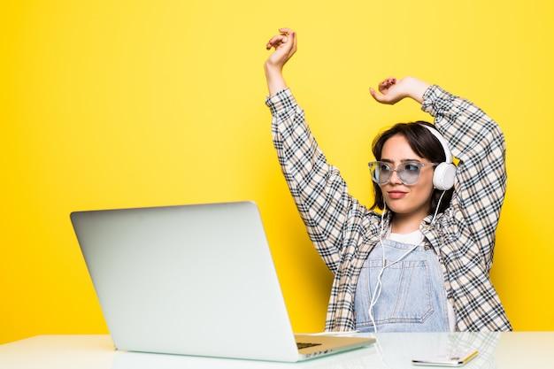 Mujer joven alegre en auriculares bailando con música mientras está sentado frente a la computadora