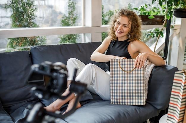 Mujer joven alegre durante el blog de moda, sosteniendo bolsas con ropa nueva