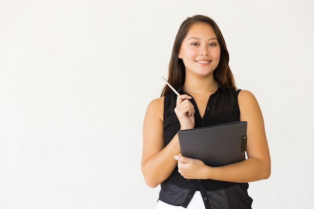 Mujer joven alegre con carpeta y pluma