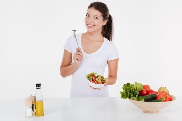 Mujer joven alegre cocinar con verduras y