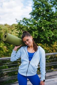 Mujer joven alegre deportes caminando en parque urbano con alfombra de fitness.