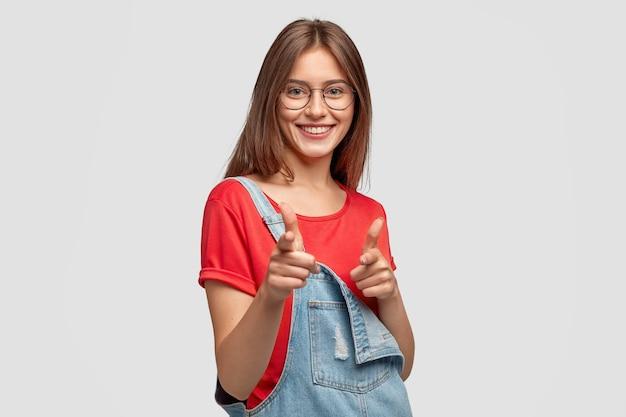 Mujer joven alegre despreocupada con cabello largo oscuro, hace gesto de pistola con ambos dedos índices, tiene una sonrisa encantadora