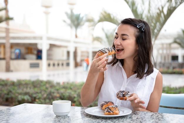 Mujer joven alegre disfrutando de un café por la mañana con donas en la terraza al aire libre.