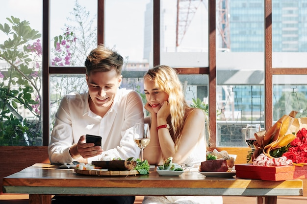 Mujer joven alegre disfrutando de una cena en la cafetería y viendo videos divertidos en el teléfono inteligente