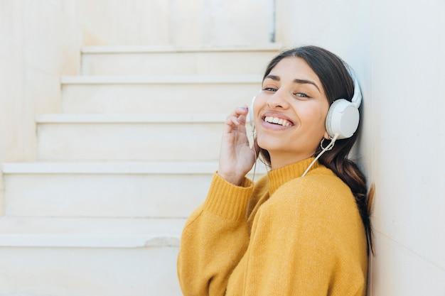 Mujer joven alegre disfrutando de la música en el auricular