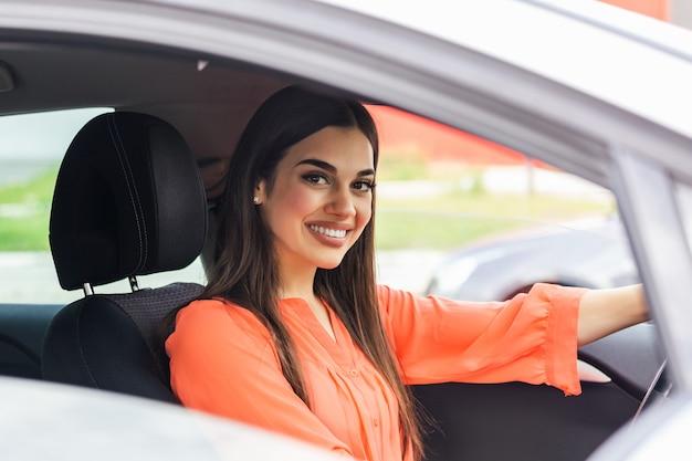 Mujer joven y alegre disfrutando de nuevo coche abrazando el volante sentado dentro