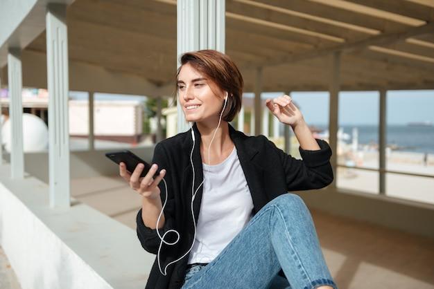 Mujer joven alegre escuchando música desde el teléfono celular en la terraza a la orilla del mar