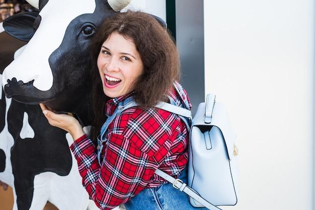 Mujer joven alegre con una estatua de cabeza de vaca en frente de la tienda.