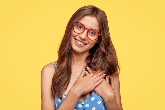 Mujer joven alegre con gafas posando contra la pared amarilla
