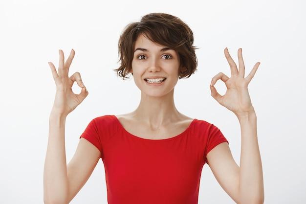 Mujer joven alegre garantiza una calidad perfecta, recomienda el producto, mostrando un gesto bien