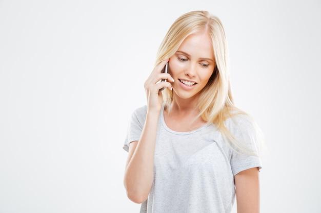 Mujer joven alegre hablando por teléfono aislado en una pared blanca