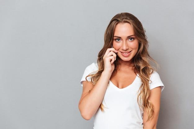 Mujer joven alegre hablando por teléfono aislado en una pared gris