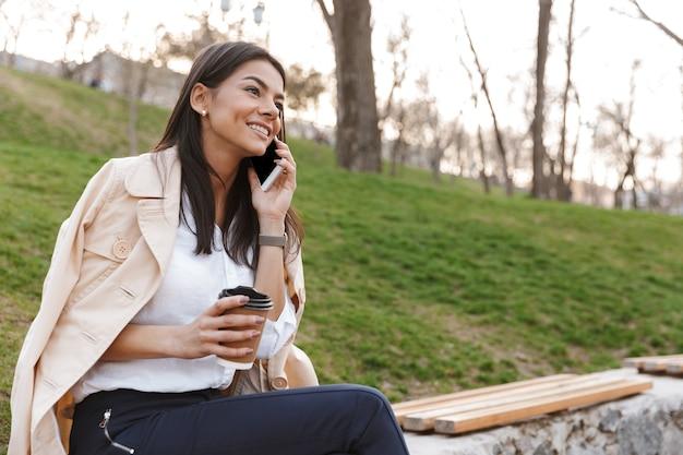 Mujer joven alegre hablando por teléfono móvil
