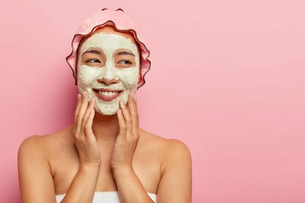 Mujer joven alegre con mascarilla facial de arcilla, recibe procedimientos de spa en un salón de belleza, mima la cara, se para envuelta en una toalla suave, disfruta del cuidado personal, usa un sombrero impermeable