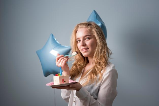 Mujer joven alegre con pastel de cumpleaños