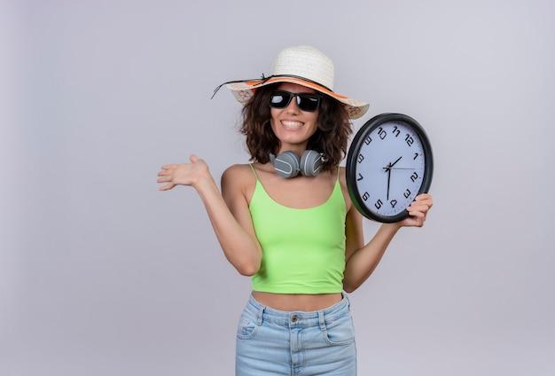 Una mujer joven alegre con el pelo corto en la parte superior verde con gafas de sol y sombrero para el sol sosteniendo un reloj de pared y mostrando adiós sobre un fondo blanco.