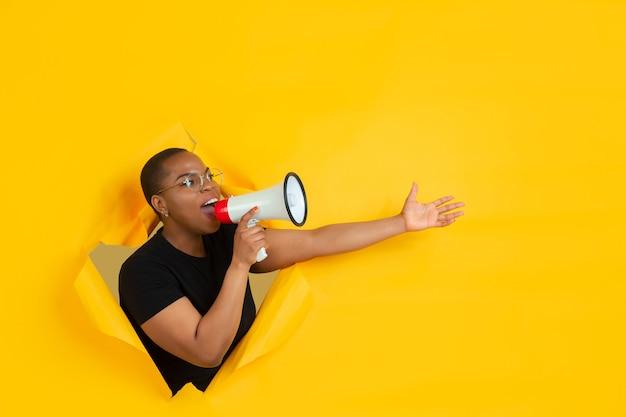 Mujer joven alegre posa en pared de agujero de papel amarillo rasgado gritos emocionales y expresivos y llamadas con altavoz