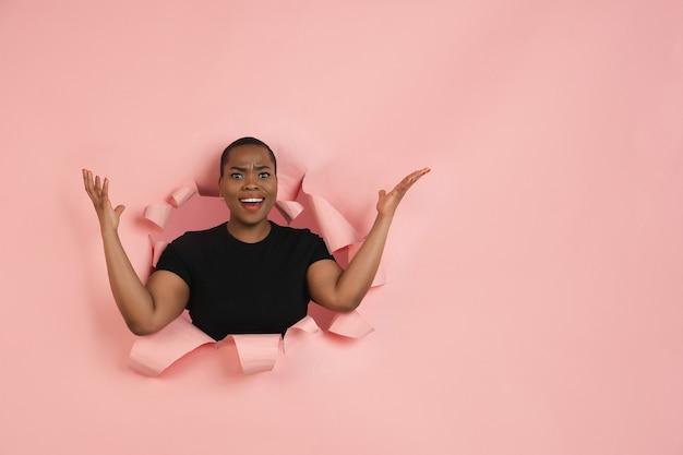 Mujer joven alegre posa en pared de agujero de papel de coral rasgado emocional y expresiva