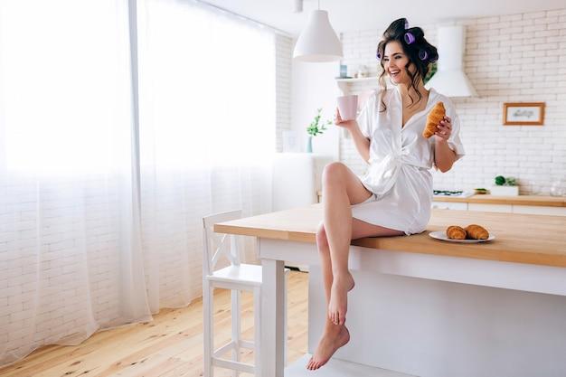 Mujer joven alegre positiva en la tabla en cocina. despreocupada ama de llaves con taza y croissant en las manos. sonrisa. solo en la cocina. sugar daddy paga por todo.