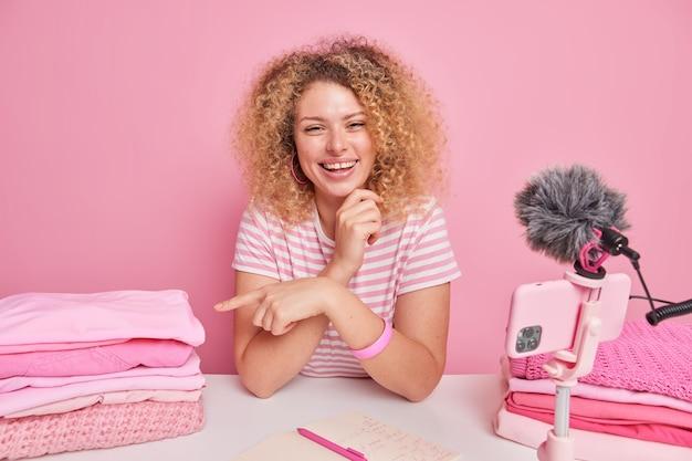 Mujer joven alegre con puntos de pelo rizado en la pila de ropa limpia doblada da consejos sobre la limpieza para sus seguidores toma notas en el bloc de notas se sienta en la mesa frente a la cámara del teléfono inteligente
