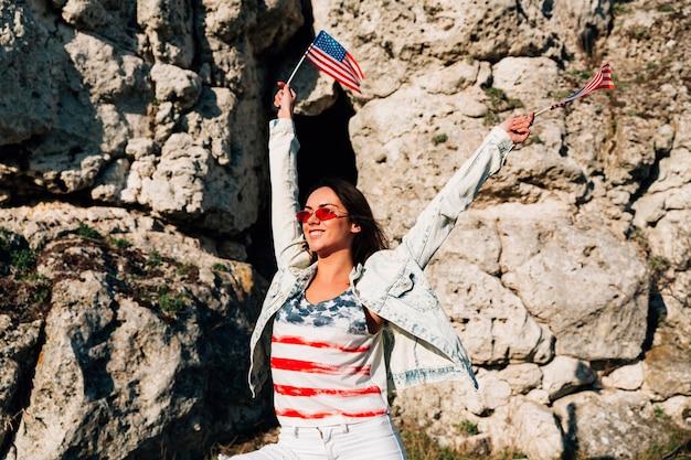 Mujer joven alegre que agita banderas americanas en rocas