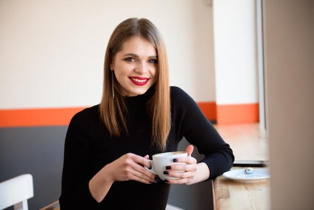 Mujer joven alegre que bebe el café caliente que lo disfruta mientras que se sienta en café.