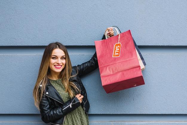 Mujer joven alegre que se coloca delante de la pared que sostiene muchos bolsos de compras coloridos