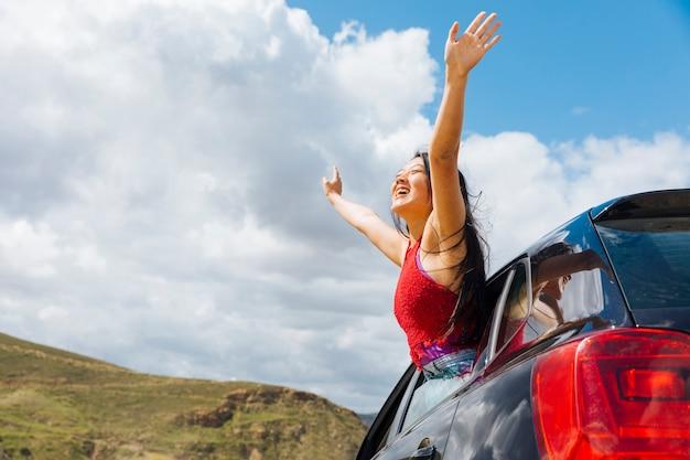 Mujer joven alegre que levanta las manos al cielo