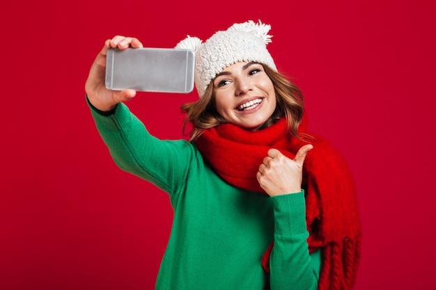 Mujer joven alegre que muestra los pulgares para arriba.