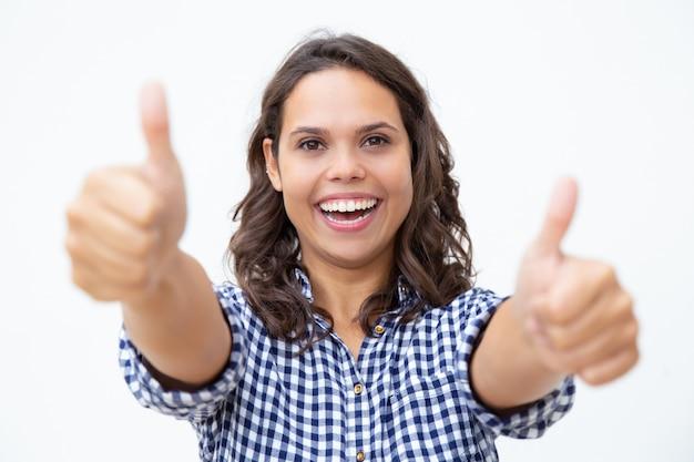 Mujer joven alegre que muestra los pulgares para arriba