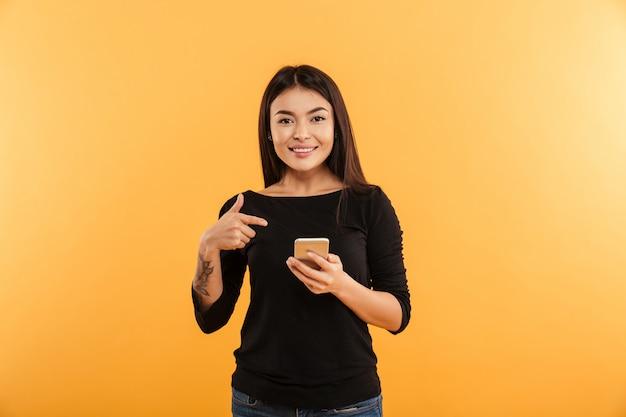 Mujer joven alegre que señala usando el teléfono móvil.