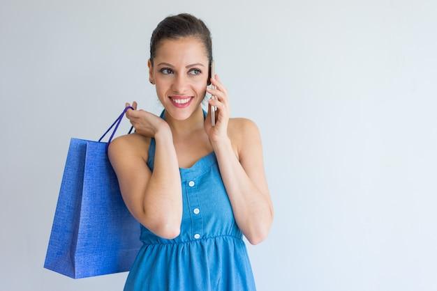 Mujer joven alegre que sostiene el panier y que invita al teléfono.