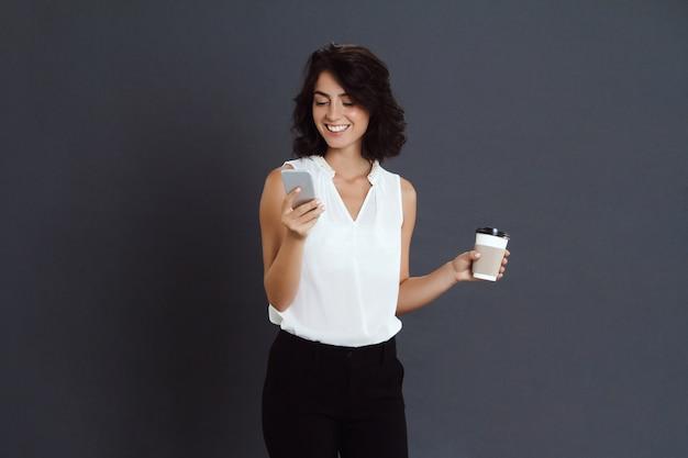 Mujer joven alegre que sostiene su teléfono y café en manos