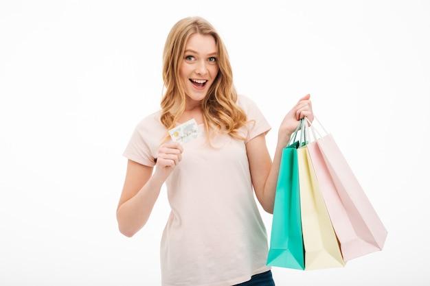 Mujer joven alegre que sostiene la tarjeta de crédito y bolsos de compras.