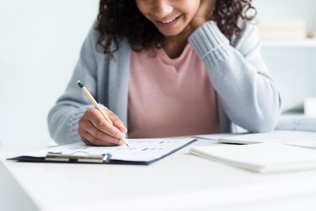 Mujer joven alegre que trabaja en lugar de trabajo