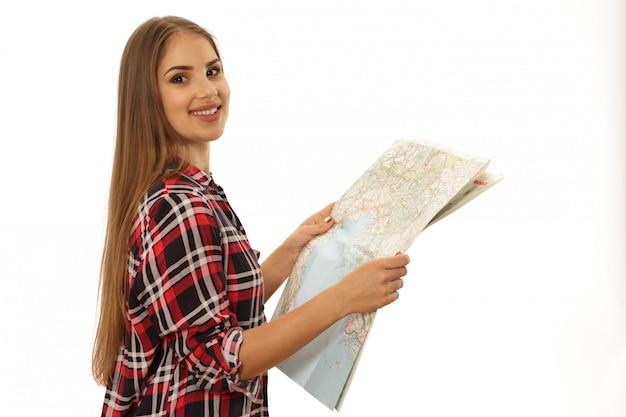 Mujer joven alegre que usa el mapa que viaja