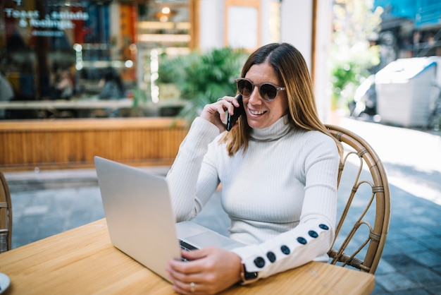 Mujer joven alegre que usa el ordenador portátil y el smartphone en la tabla en café de la calle