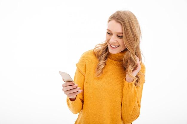 Mujer joven alegre que usa el teléfono móvil.