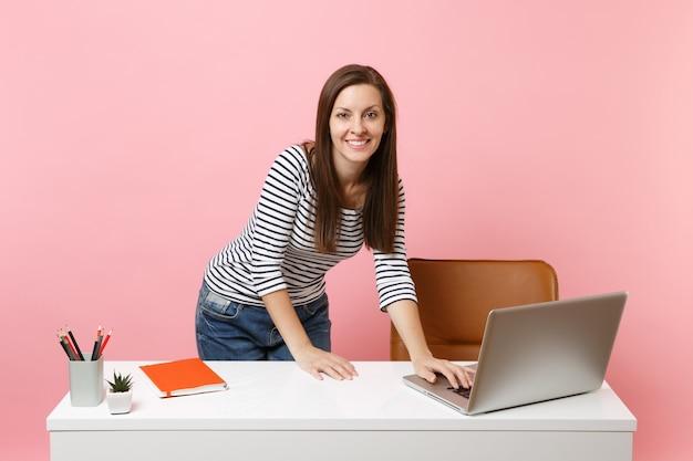 Mujer joven alegre en ropa casual de pie cerca del escritorio blanco trabajando en un portátil pc contemporáneo