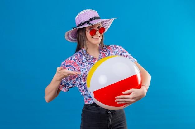 Mujer joven alegre con sombrero de verano con gafas de sol rojas sosteniendo una bola inflable apuntando con el brazo de la mano a ella sonriendo con cara feliz de pie sobre el espacio azul