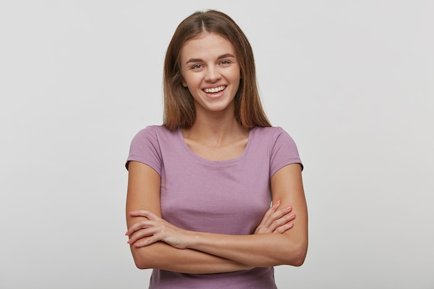 Mujer joven alegre con una sonrisa agradable, tiene el pelo largo y castaño, piel sana, viste una camiseta informal, se para con las manos cruzadas